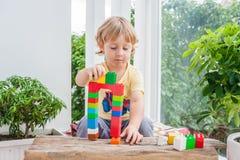Netter Kleinkindjunge mit dem Spielen mit vielen buntem Plastik blockiert Innen Aktives Kind, das Spaß mit Gebäude hat und O scha Lizenzfreie Stockfotografie