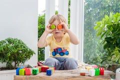 Netter Kleinkindjunge mit dem Spielen mit vielen buntem Plastik blockiert Innen Aktives Kind, das Spaß mit Gebäude hat und O scha Stockbilder