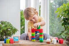Netter Kleinkindjunge mit dem Spielen mit vielen buntem Plastik blockiert Innen Aktives Kind, das Spaß mit Gebäude hat und O scha Lizenzfreies Stockbild
