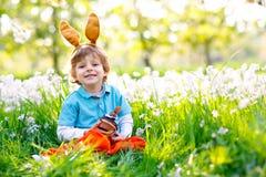 Netter Kleinkindjunge mit den Osterhasenohren das glückliche Kind des traditionellen Festes feiernd, das an Schokoladenkuchen des lizenzfreie stockfotografie