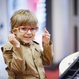 Netter Kleinkindjunge am Optikerspeicher während des Wählens seines neuen gl lizenzfreies stockfoto