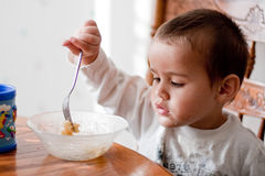 Netter Kleinkindjunge speist Selbst Stockbild