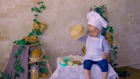 Netter Koch des Babys männliches Kinderim Küchenleichten schlag der Teller stock footage