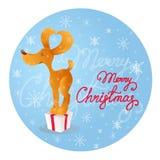 Netter lächelnder gelber Hund, der auf der Geschenkbox steht Blauer Hintergrund mit Schneeflocken Frohe Weihnachten Lizenzfreies Stockbild