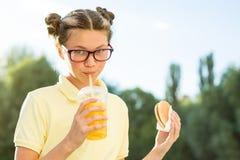 Netter lächelnder Jugendlicher in der Schuluniform, die einen Hamburger hält und Lizenzfreies Stockfoto
