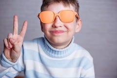 Netter lächelnder Junge in der orange Sonnenbrille mit dem undurchsichtigen Linsendarstellen stockfotografie