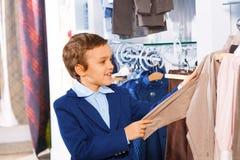 Netter lächelnder Junge steht nahe Kleidung und das Wählen stockbild