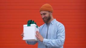 Netter lächelnder junger Mann, der ein Geschenk auf orange Hintergrund, Zeitlupe fängt stock video footage