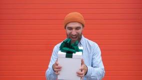 Netter lächelnder junger Mann, der ein Geschenk auf orange Hintergrund, Zeitlupe fängt stock video