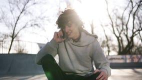 Netter, l?chelnder junger Mann nennt zu den Freunden, die Handy beim Sitzen in einer Rochenzone im Rochenpark verwenden Ein Kerl stock video footage