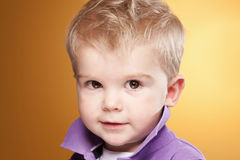 Netter lächelnder kleiner Junge, der Kamera betrachtet Stockbilder