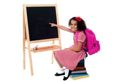 Netter lächelnder Student, der auf leere Tafel zeigt Stockfotografie