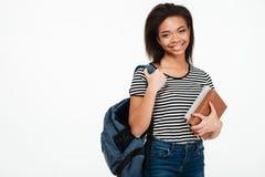 Netter lächelnder tragender Rucksack des afrikanischen Studentenmädchens und halten Bücher stockbild