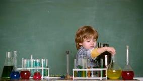 Netter l?chelnder kleiner Junge, der Spa? gegen blaue Wand hat Eine Chemiedemonstration Was in der Chemie unterrichtet wird schul stock video