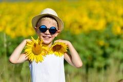 Netter lachender blonder Junge in den Sonnenbrillen und im Hut mit Sonnenblumen auf Feld draußen Lizenzfreie Stockbilder