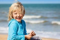 Netter lachender Junge am Strand Stockbild