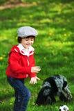 Netter lachender Junge und sein Hund, spielend im Park, Frühjahr Stockfotografie