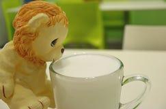 Netter Lion Toy Drinking Warm Milk von der transparenten Glasschale Stockfotografie