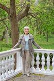 Netter älterer Frauensenior auf der Veranda im Park Stockbilder