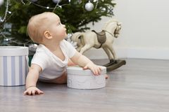 Netter lustiger Junge unter Weihnachtsbaum in Erwartung eines Wunders Lizenzfreie Stockfotos