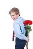 Netter lustiger kleiner Junge, der rote Rosen hinter seinem hinteren Lächeln hält Lizenzfreie Stockfotografie
