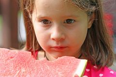 Netter Mädchen Brunette isst eine enorme Scheibe der roten Wassermelone Lizenzfreie Stockfotografie