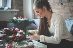Netter Mädchen-Dekorateur mit Weihnachtsdekorationen stockbild