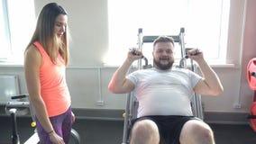 Netter Mädchentrainer erklärt einem kaukasischen Mann die Korrektheit des Handelns einer Übung für Beinmuskeln auf einem hackensh stock video footage