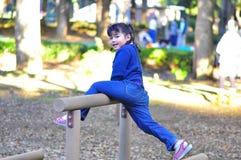 Netter Mädchenversuch, zum der höheren Planke am Spielplatz zu erreichen Stockbild