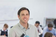 Netter männlicher Lehrer, der in seinem Klassenzimmer steht Lizenzfreie Stockfotos