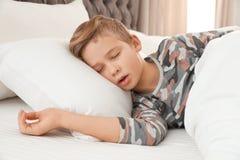 Netter müder Junge, der im Bett schläft lizenzfreie stockbilder