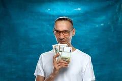 Netter Mann, der auf blauem Hintergrund aufwirft Lizenzfreie Stockfotos