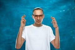 Netter Mann, der auf blauem Hintergrund aufwirft Stockfotos