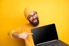 Netter Mann, der auf Laptop zeigt lizenzfreies stockfoto