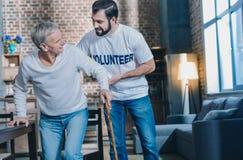 Netter netter Mann, der einem gealterten Mann hilft Stockbild