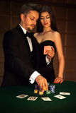Netter Mann in der eleganten Klage, die Karten mit seiner sexuellen Frau schaut und stockfoto