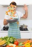 Netter Mann, der Gemüse in der Küche wirft lizenzfreie stockfotos