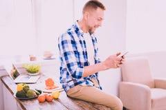 Netter Mann, der am Telefon in der Küche plaudert stockfotos