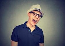 Netter Mann in einem weißen Hut blinzelnd über grauem Wandhintergrund lizenzfreies stockfoto