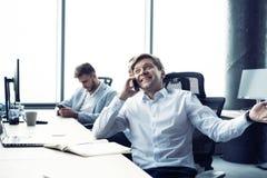 Netter Mann im B?ro, welches das Telefon beantwortet lizenzfreie stockfotos