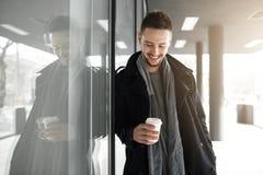 Netter Mann im schwarzen Mantel, der Weißbuchschale hält stockbilder