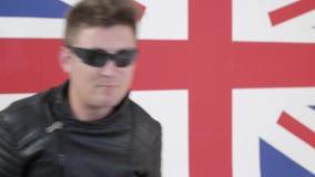 Netter Mann mit kühlem Haarschnitt und Sonnenbrille in der Motorradjacke singt und tanzt stock video footage