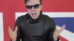 Netter Mann mit Sonnenbrille in der ledernen Motorradjacke tanzt aktiv auf Kamera stock video