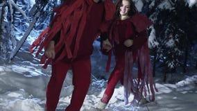 Netter Mann und die Frau, die in den roten Kostümen gekleidet wird, haben Spaß im Holz des verschneiten Winters stock video