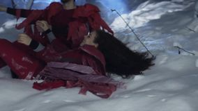 Netter Mann und die Frau, die in der roten Kleidung gekleidet wird, sitzen auf Schnee im Winterwald stock footage