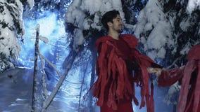 Netter Mann und die Frau, die in der roten Kleidung gekleidet wird, ziehen langsam in Holz des verschneiten Winters um stock footage