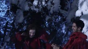 Netter Mann und Frau ziehen langsam in Holz des verschneiten Winters nachts einfrierendes um stock footage