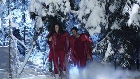 Netter Mann und weibliche tragende rote Kleidung, die sich langsam in Wald des verschneiten Winters bewegt stock video footage
