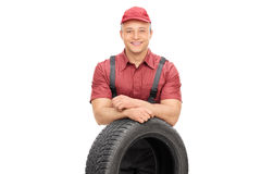 Netter Mechaniker, der hinter einem Autoreifen steht Stockfotografie