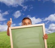 Netter mexikanischer Junge gibt Daumen oben auf dem Gebiet, das leeres Kreide-Brett hält Stockfoto